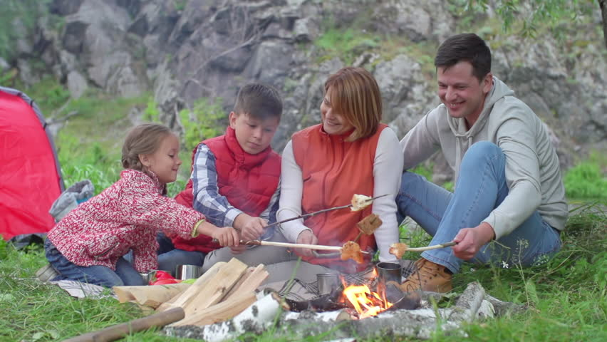 Mother Father Son And Little Daughter Making Bread Over Campfire Talking