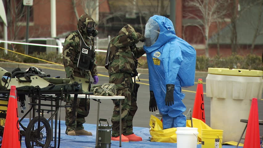 Zipping a HAZMAT team member into a protective suit  during a nuclear or biological disaster preparedness drill.