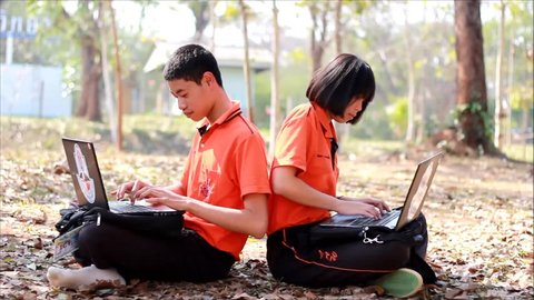 Students sitting and learning computer laptop on lawn in high school at LOEI Province, THAILAND.