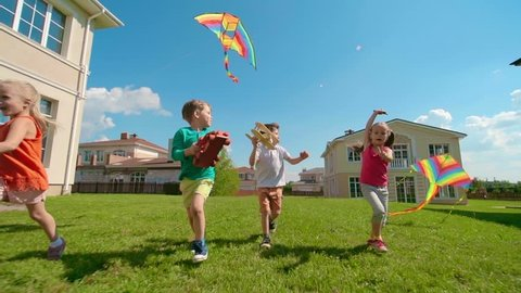Four kids are running on green grass: two girls flying kites, boys holding wooden toys