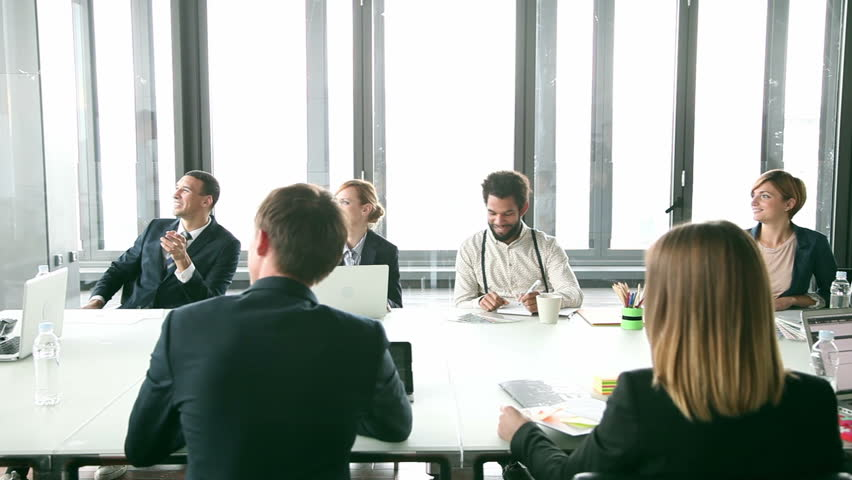 Happy business people sitting at table in conference room and listening presentation, graded | Shutterstock HD Video #15456565