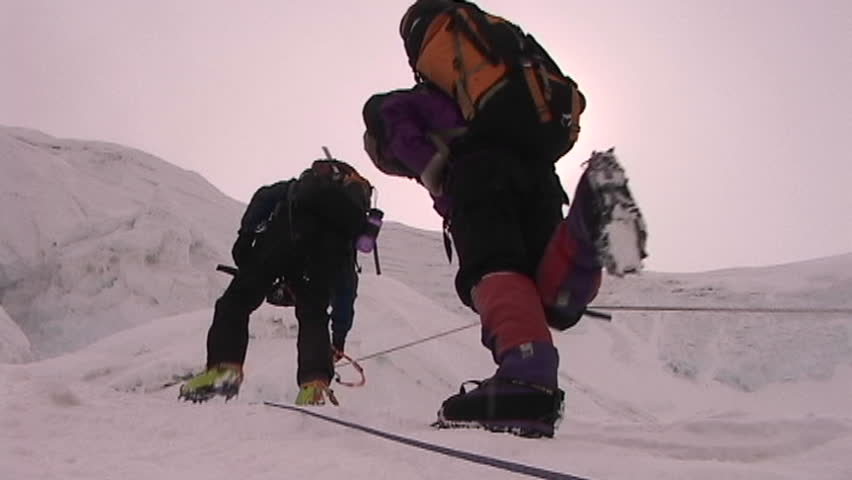 The sun beats down on climbers as they ascend icy slope