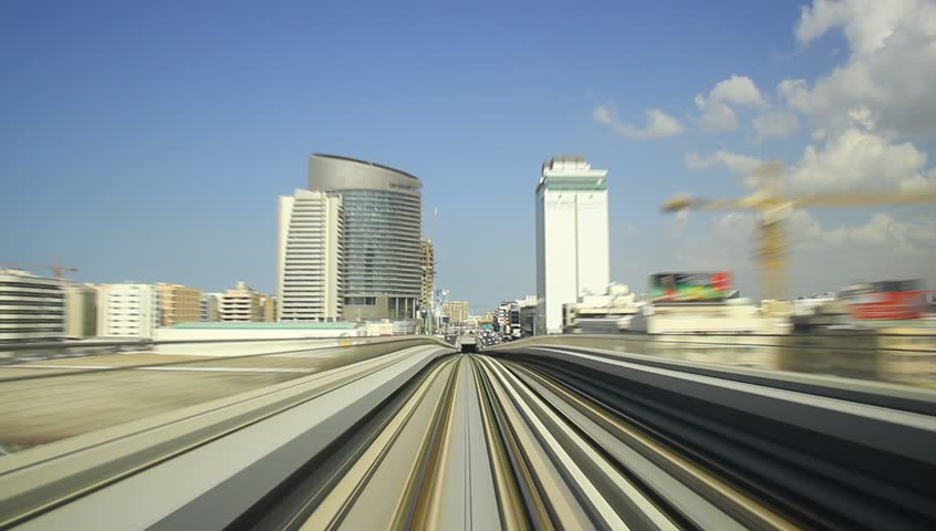 Dubai metro POV time lapse view from rear cabin. Train quickly ride from BurJuman underground station, at red line, pass downtown area and Business Bay overground station. Blue sky with light clouds