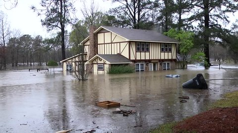 HAUGHTON, LOUISIANA, U.S.A. - MARCH 9, 2016: Flooded home in Tall Timbers subdivision, Bossier Parish, La., during historic floods, March 9, 2016. Neighbor evacuates children.