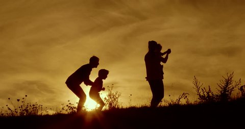 Happy family fun silhouetted dawn with orange sky