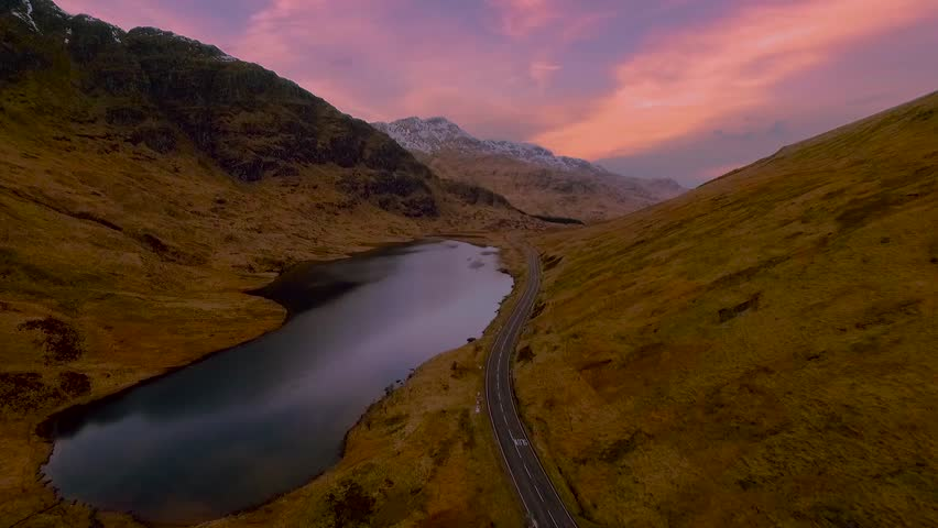 Aerial shot of road and lake in Scottish highlands with pink and blue sky at dusk