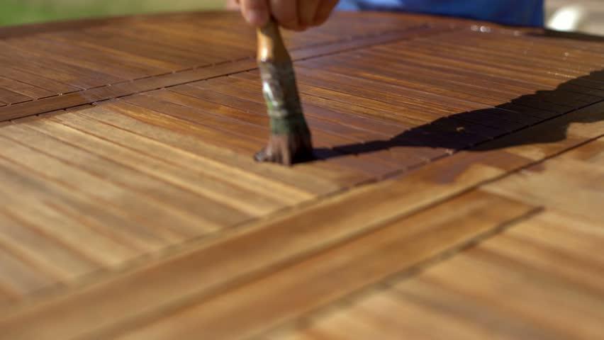 closeup shot of restorer restoring a wooden table varnishing with a mordant garden furniture - Garden Furniture Varnish