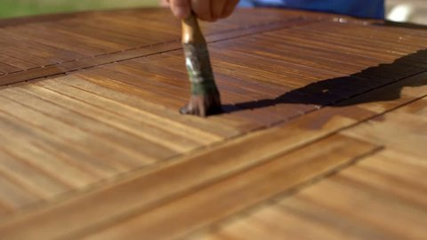 Closeup shot of restorer restoring a wooden table varnishing with a mordant. Garden furniture.