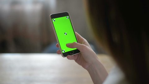 Young Girl is Holding Smartphone with Green Screen at Evening Time.