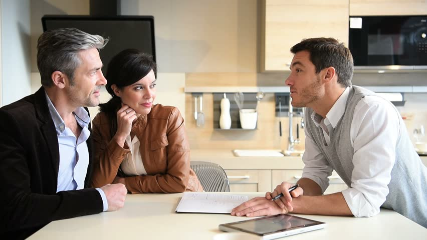 Couple In Real Estate Agency Talking To Businessman. Portrait Of