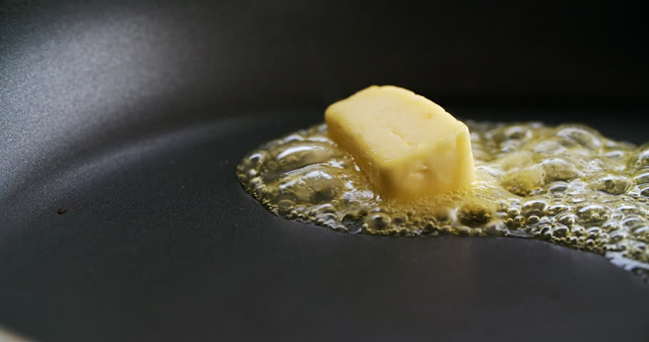 Cube of butter melting sizzling browning in non stick pan skillet in slow motion, preparation for cooking