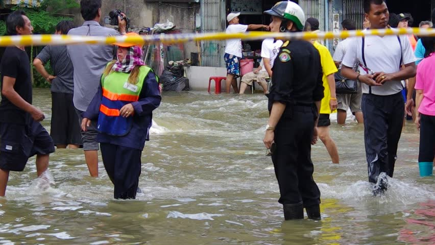 BANGKOK - OCT 30: Unidentified residents of Bangkok's Dusit district make their way through flooded streets after the Chao Phraya River bursts its banks on Oct 30, 2011 in Bangkok, Thailand.