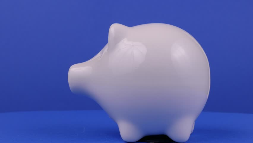 Currency and piggy bank on a blue background  | Shutterstock HD Video #15622162
