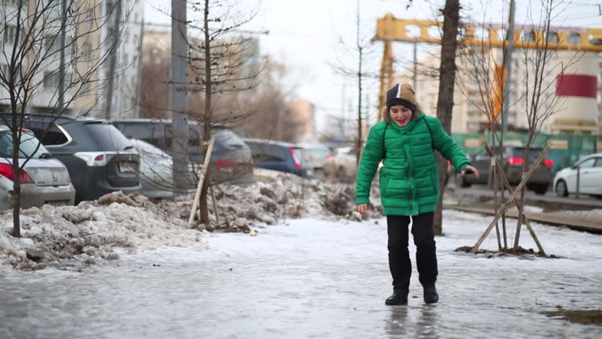 Boy runs, slips and falls down on icy surface, girl helps him to stand up.