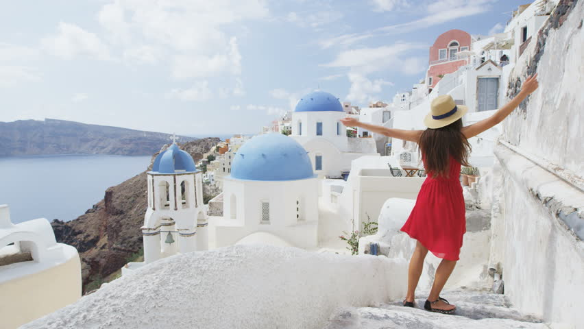 Happy woman tourist having fun swirling around in joy on Santorini. Young woman is wearing red dress and sunhat enjoying her Europe vacation on the famous Greek island sightseeing travel destination.