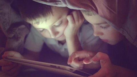 Two kids using tablet pc under blanket at night. Brothers with tablet computer in a dark room. Slow motion HD 1080p
