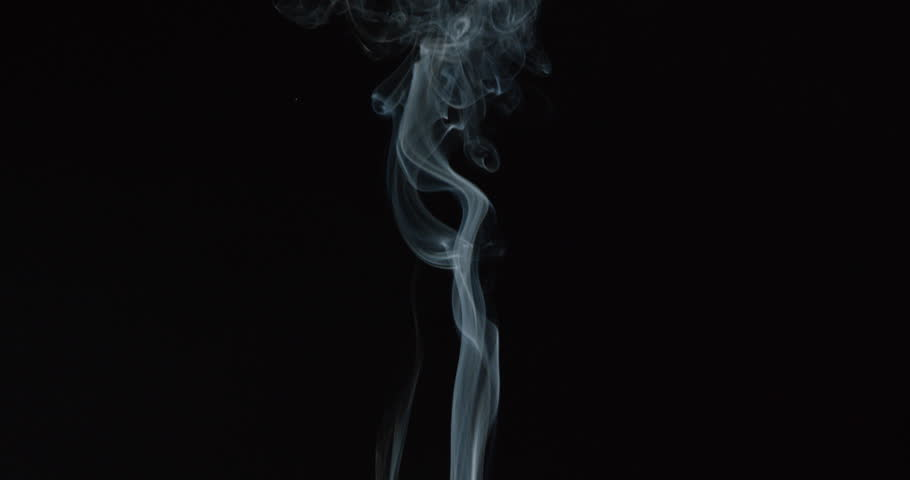 elegant wisps of smoke rise from burning paper in glass against black background stock footage