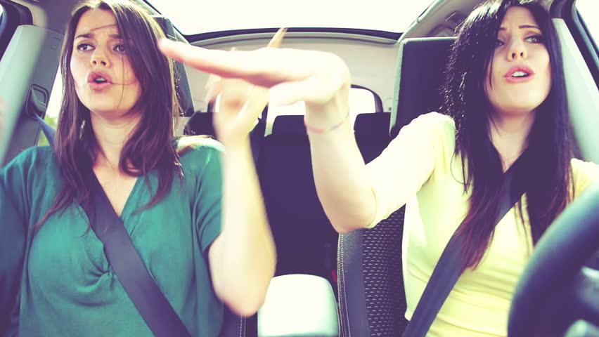 Gorgeous women dancing like crazy driving car retro look