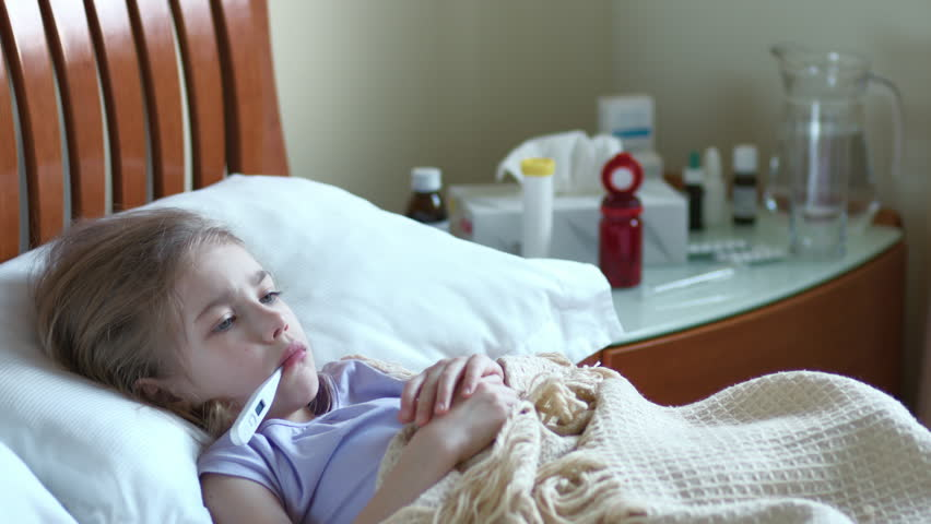 little sick boy sitting in bed with medicine in foreground