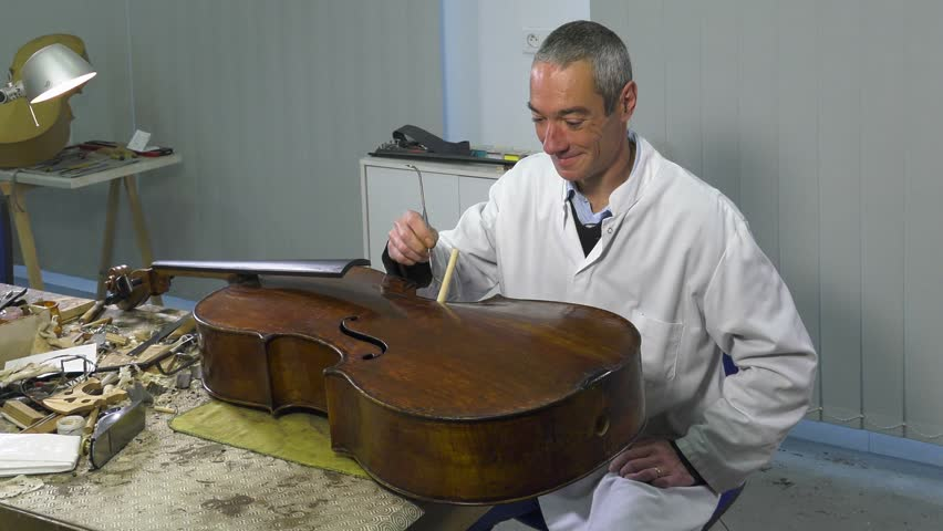 luthier uses special tools to put under presure the soul of the cello