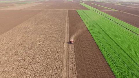 Tractor cultivating arable land for seeding crops, aerial view