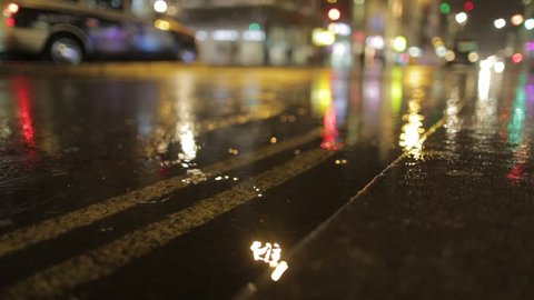 Low Shot of puddle whilst it rains with taxi