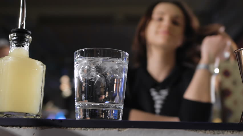 attractive girl in a good mood, sitting at the bar, with a glass in her hand.