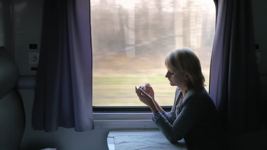 Always connected - woman enjoying a phone on the train