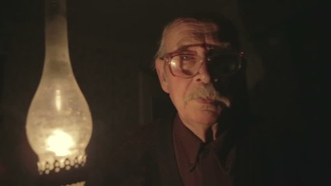 The face of the poor old grandfather with a kerosene lamp in hand, walking in the night