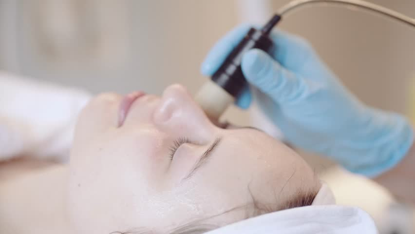Young Woman getting a cosmetic medicine spa treatment, close up. 4K UHD, Slow Motion. Beautician hands at work, providing led light skin treatment therapy to a girl face. Special beauty equipment.   Shutterstock HD Video #15803452