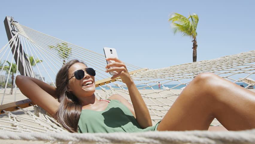 Happy beach woman reading sms texting on smartphone lying on hammock relaxing on tropical vacation. Young casual cute girl lying down in outdoor swing bed enjoying sun sunbathing using mobile phone.