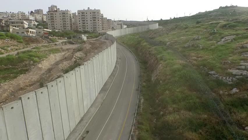 Flight close to security fence in Jerusalem Drone flight view of east Jerusalem security wall divide between Israeli and Arab neighborhood