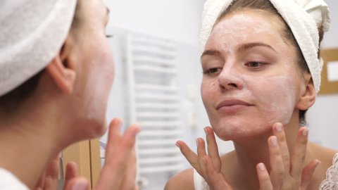 Woman applying mask moisturizing skin cream on face looking in bathroom mirror. Girl taking care of her complexion layering moisturizer. Skincare spa treatment. 4K ProRes HQ codec