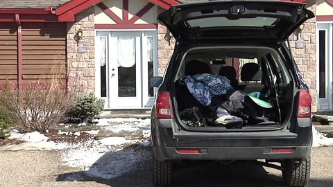 August 07,2012: Three young people packing boot of car ready for skiing