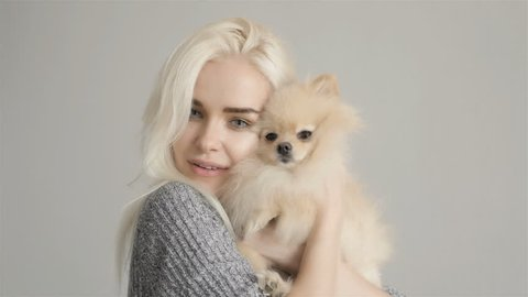 Beautiful Blonde Woman With Her Spitz Isolated On Grey