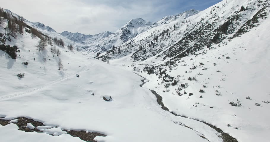 An aerial view over a winter valley in Livigno, full of white snow, white mountain
