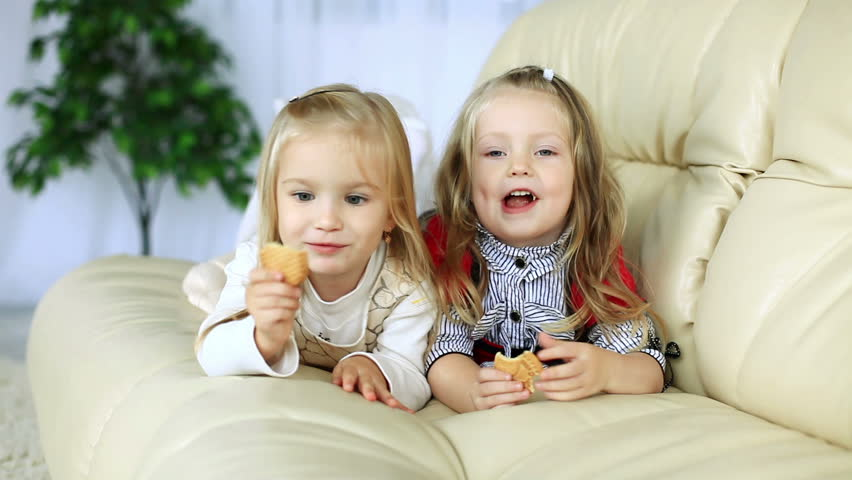 Little sisters lying on the couch eating cookies. DOLLY HD