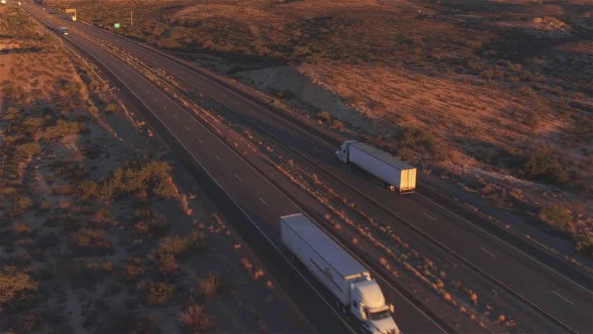 4K AERIAL: Flying high above container semi truck transporting goods on busy highway across the country in beautiful summer evening. Traffic driving and speeding on busy freeway at golden sunset