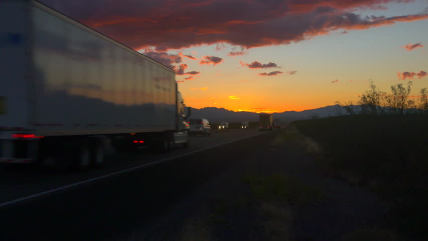 4K CLOSE UP: Personal cars and big freight transporting semi trucks driving on busy highway at beautiful golden sunrise in summer. Traffic on busy freeway speeding in colorful early morning