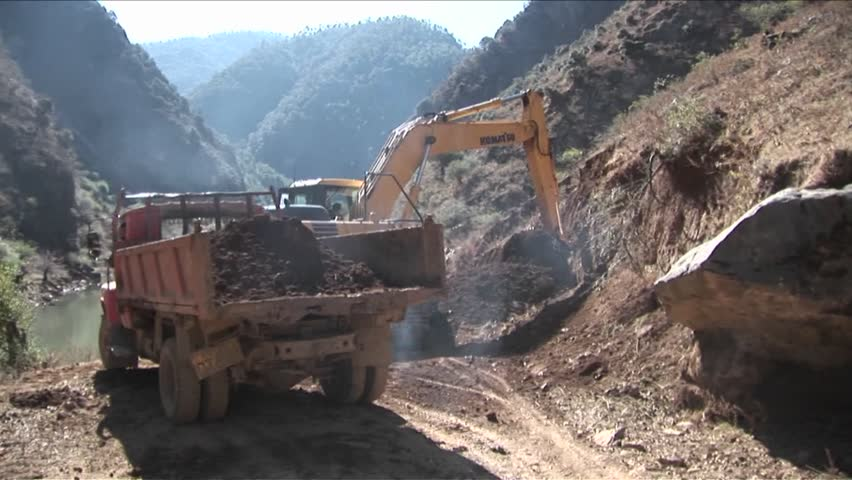 A steam shovel moves earth into a dump truck along a rural road
