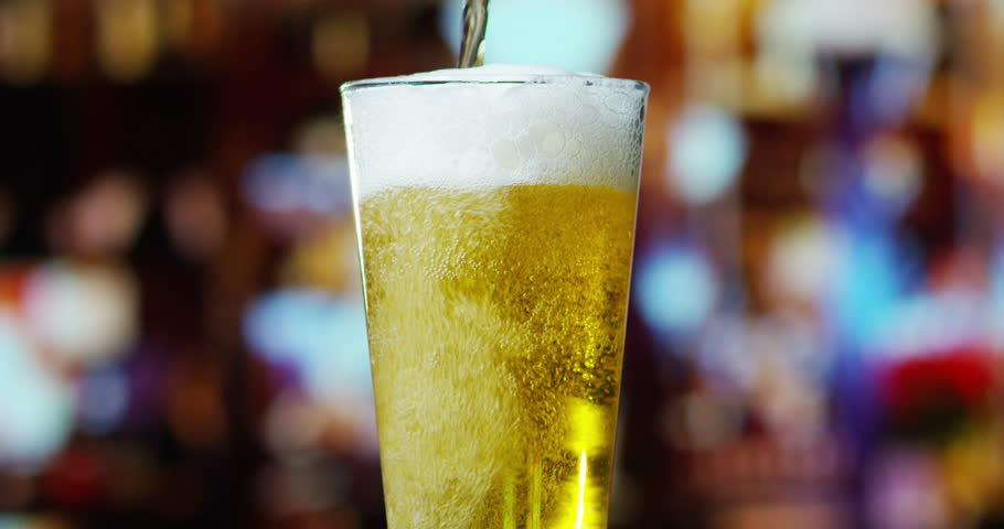 Beer is pouring from the top into the glass forming waves | Shutterstock HD Video #15964765