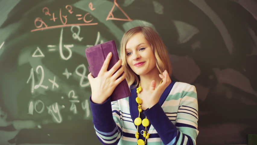 Teacher standing in the class and looking on tablet    Shutterstock HD Video #15966502