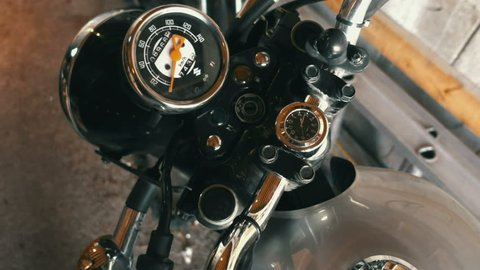 First person view of a person putting a key into a motorcycle ignition and turning it on.