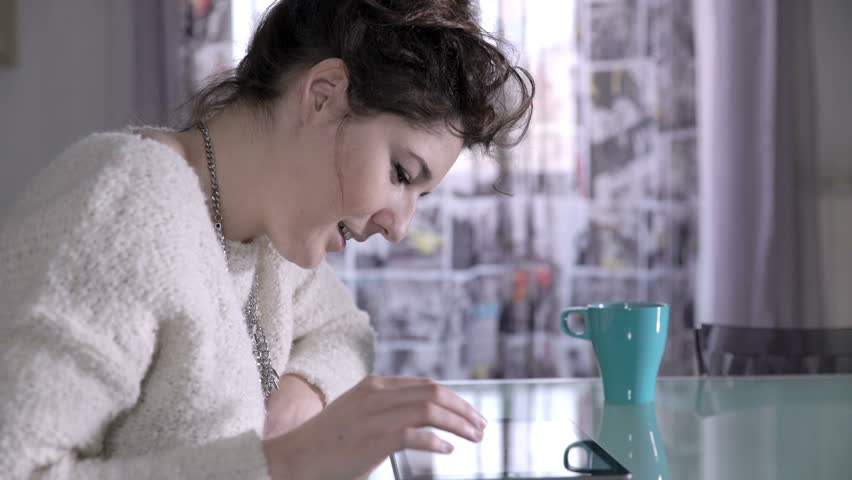 Woman sat at home takes a cup of tea and browse the web with her tablet | Shutterstock HD Video #15991612