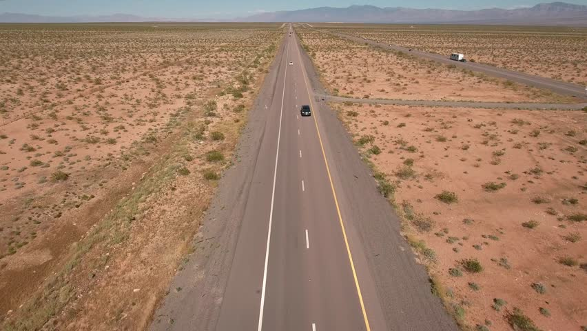 An aerial shot of cars and trucks traveling through the desert of Nevada near Las Vegas on Interstate 15 | Shutterstock HD Video #16022122