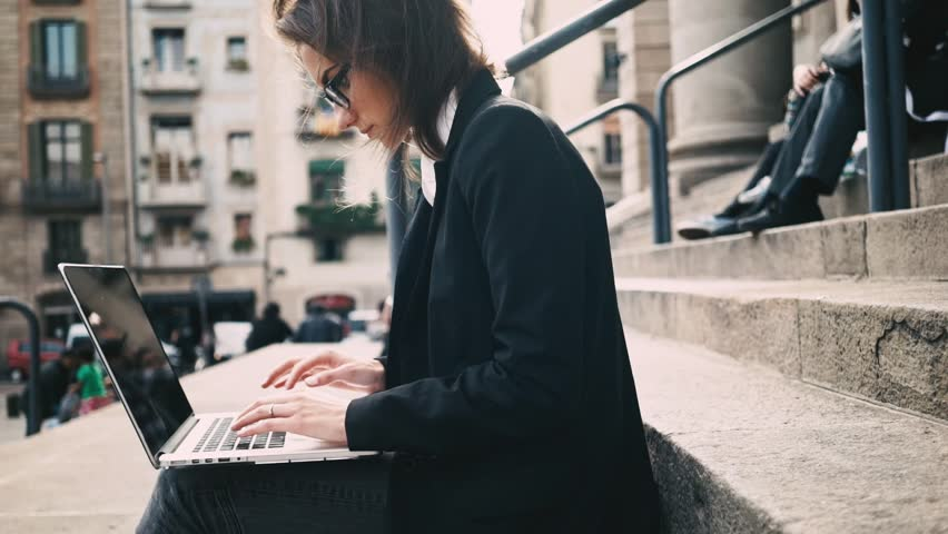 Side view of young attractive female student sitting on the stairs of University and using modern laptop, businesswoman typing on computer keyboard while working on a break outdoors, slow motion