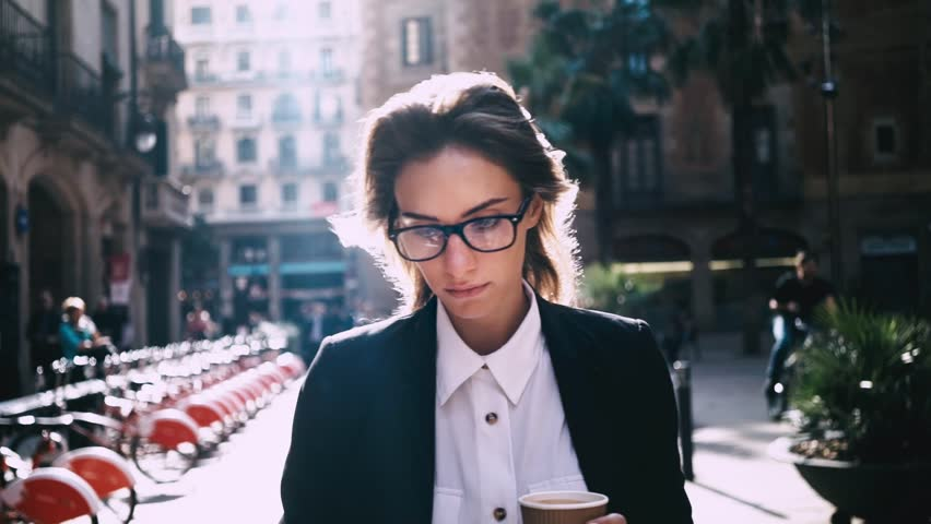 Close-up of attractive young businesswoman walking on urban street and using modern smartphone outside, sunshine, slow motion | Shutterstock Video #16045882
