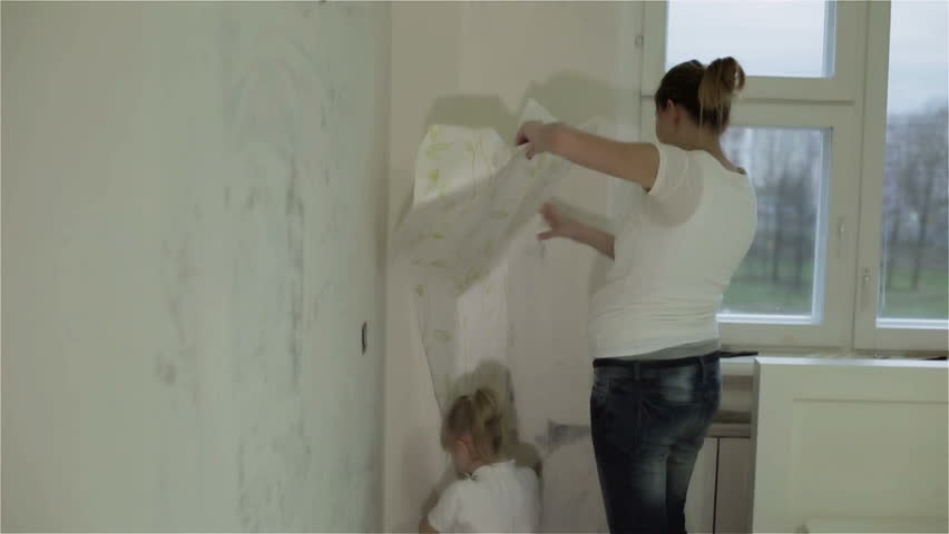 A mother and a daughter removing wallpaper, clapping and hugging. A pregnant mother and a small daughter removing wallpaper near a window, clapping hands and hugging. #16051222