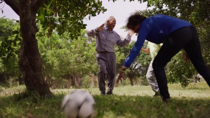 Old and young people, seniors and children, child and elderly persons. Sports fun, child playing football game with grandparents, soccer in park, happy old man kicking ball, recreation and leisure