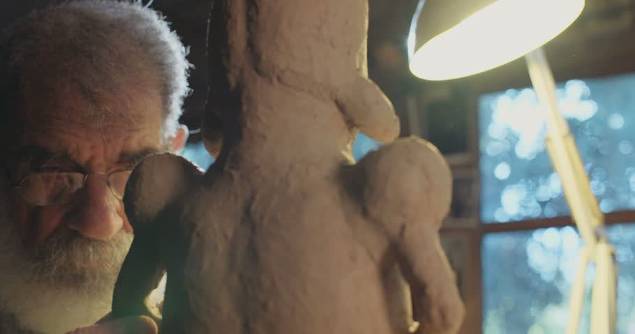 Old artist modeling a clay sculpture in his small studio | Shutterstock HD Video #16091002